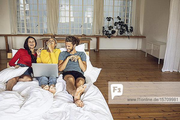Glückliche Freunde entspannen sich zu Hause im Bett und schauen einen Film auf dem Laptop an