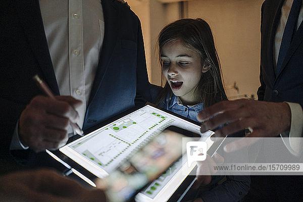 Geschäftsleute und Mädchen betrachten glänzenden Bauplan auf Tablett im Büro