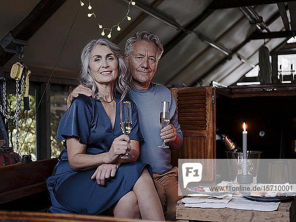 Porträt eines älteren Ehepaares bei einem Candlelight-Dinner auf einem Boot im Bootshaus