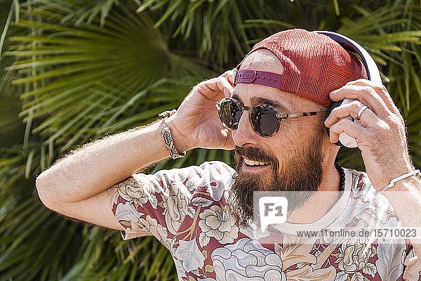 Lächelnder reifer Mann mit roter Basecap  Sonnenbrille und weißen Kopfhörern