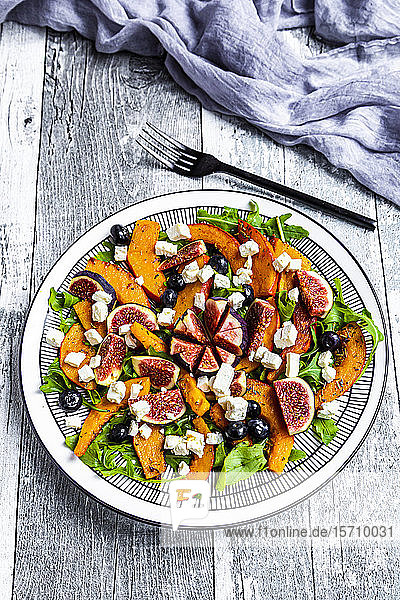 Plate of colorful autumnal salad with figs  feta cheese  arugula  blueberries and Hokkaido squash