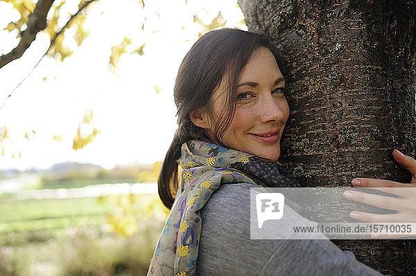 Porträt einer Frau  die einen Baum umarmt