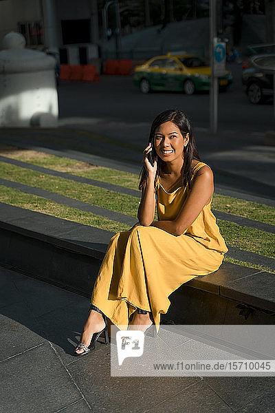 Porträt einer lächelnden Frau am Telefon in der Stadt