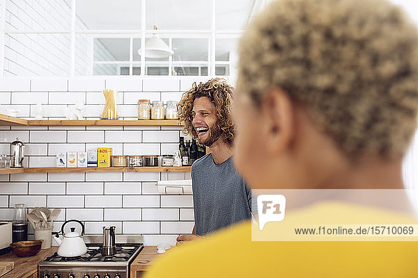 Lachender Mann mit Frau in der heimischen Küche