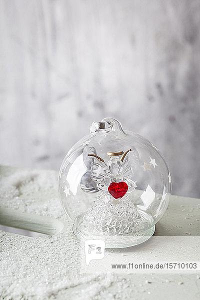 Nahaufnahme einer gläsernen Weihnachtskugel mit Engelsfigur im Inneren und rotem Herz