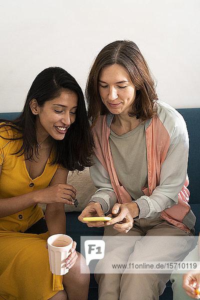 Zwei Frauen sitzen auf der Couch und teilen sich ein Mobiltelefon