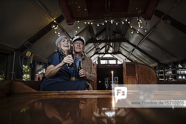 Happy senior couple having a drink on a boat in boathouse
