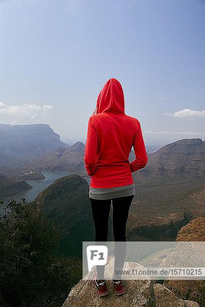 Frau  die auf einem Felsen steht und die wunderschöne Landschaft unter sich genießt  Blyde River Canyon  Südafrika.