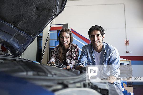 Junge Frau und Mann stehen im Servicezentrum neben dem Auto  lächeln in die Kamera und arbeiten im Team