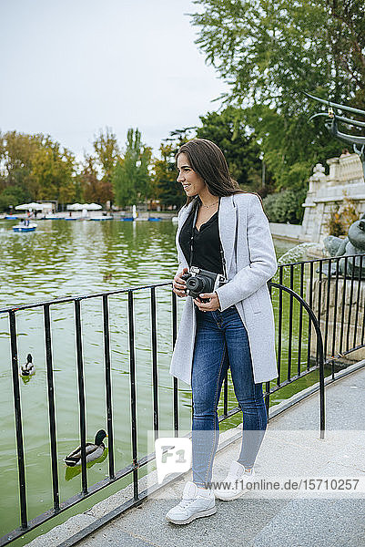 Woman with camera standing at a lake in El Retiro park  Madrid  Spain