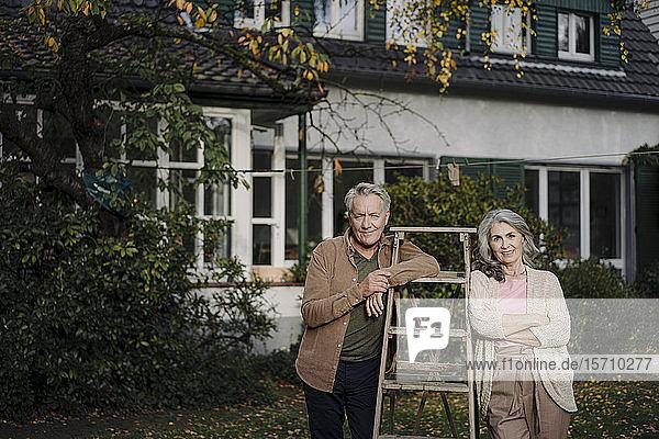 Porträt eines älteren Ehepaares mit einer Leiter im Garten ihres Hauses
