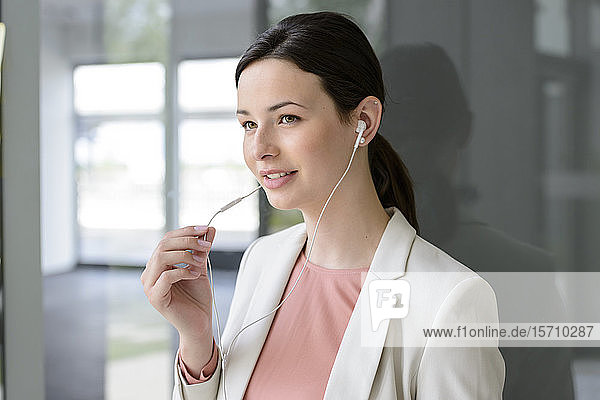 Smiling young businesswoman with earphones in office