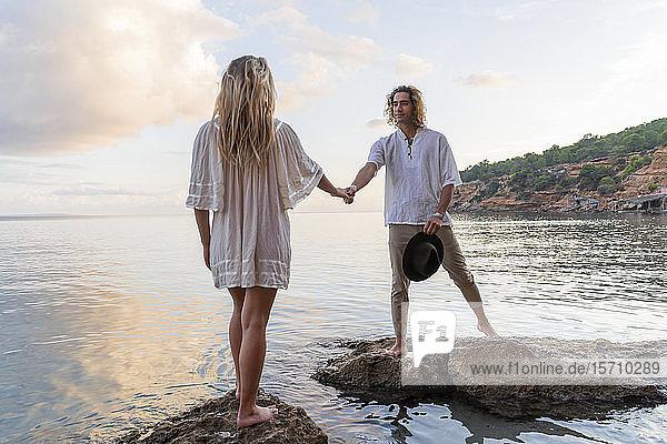 Junges Paar steht auf Felsen vor dem Meer und hält sich an den Händen  Ibiza  Balearen  Spanien