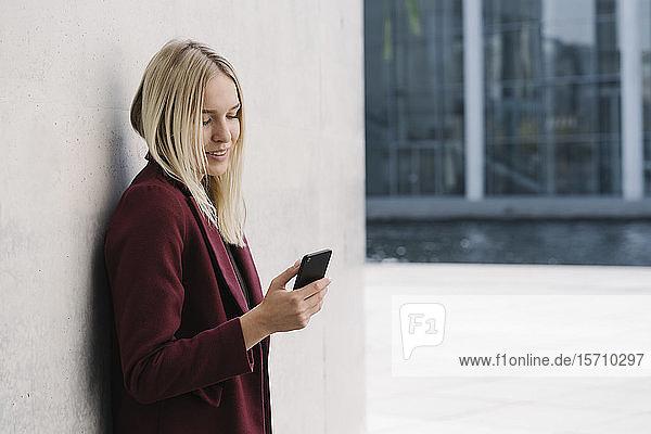 Blonde Geschäftsfrau mit Smartphone  an einer Wand lehnend  nach unten blickend