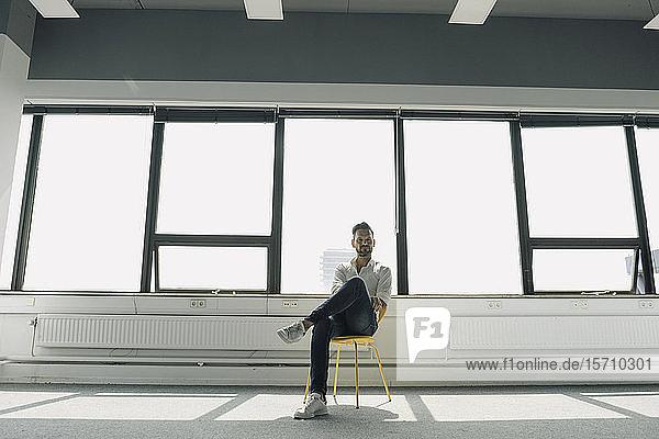 Reifer Geschäftsmann sitzt auf gelbem Stuhl in leerem Büro