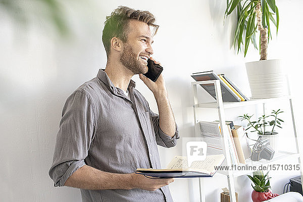 Smiling man on the phone in office