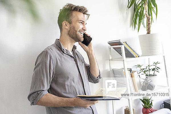 Lächelnder Mann am Telefon im Büro
