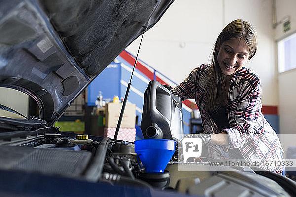 Lächelnde Gelegenheitsfrau mit Handschuhen  die eine Dose Motoröl in der Hand hält und es durch einen Trichter in ein in Betrieb befindliches Auto gießt