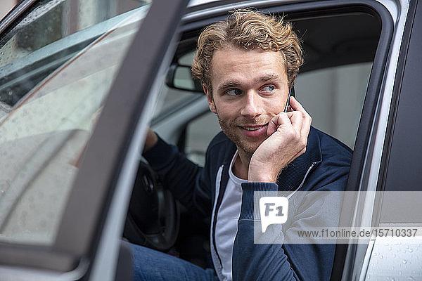 Junger Mann telefoniert und sitzt im Auto  schaut zur Seite