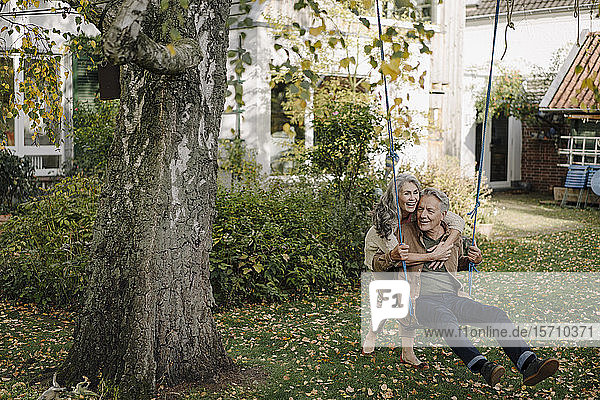 Happy woman embracing senior man on a swing in garden