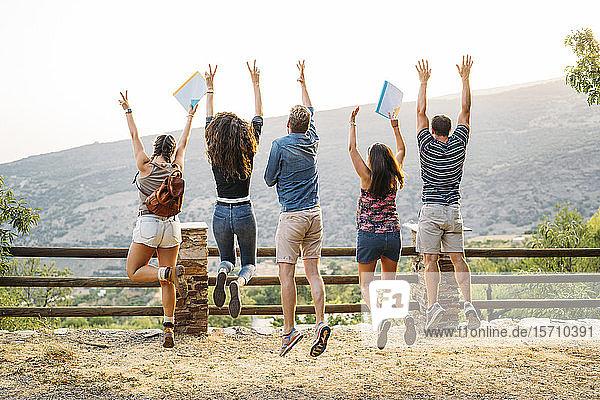 Rückansicht von glücklichen Freunden  die in die ländliche Landschaft springen