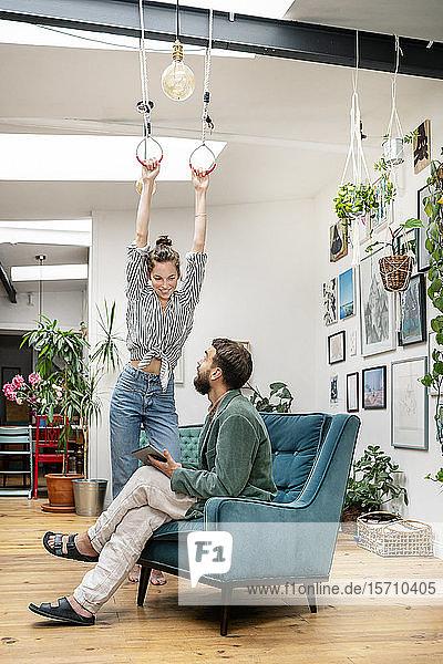 Junges Paar sitzt im Sessel und unterhält sich