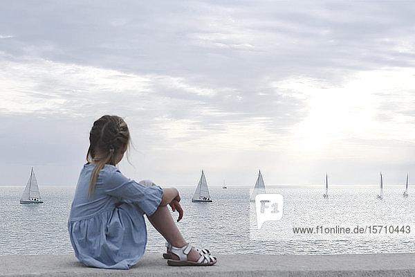 Kleines Mädchen schaut mit Booten aufs Meer Kleines Mädchen schaut mit Booten aufs Meer
