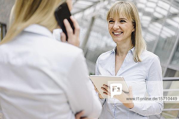 Porträt einer jungen Geschäftsfrau mit Tablette  die ihren Amtskollegen anlächelt