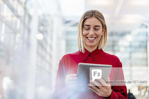 Glückliche junge Geschäftsfrau trägt rotes Hemd mit Tablette