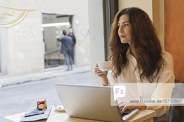 Young woman with laptop in a cafe