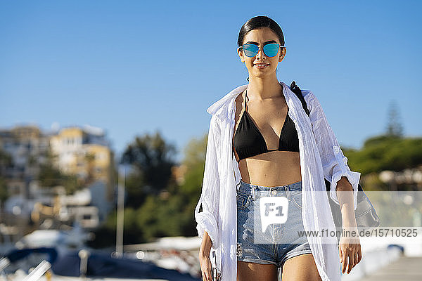 Porträt einer jungen Frau beim Spaziergang in einem Yachthafen