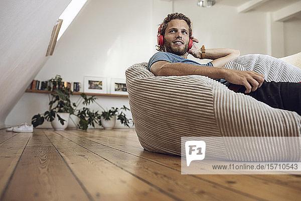 Junger Mann entspannt sich zu Hause im Sitzsack und hört Musik