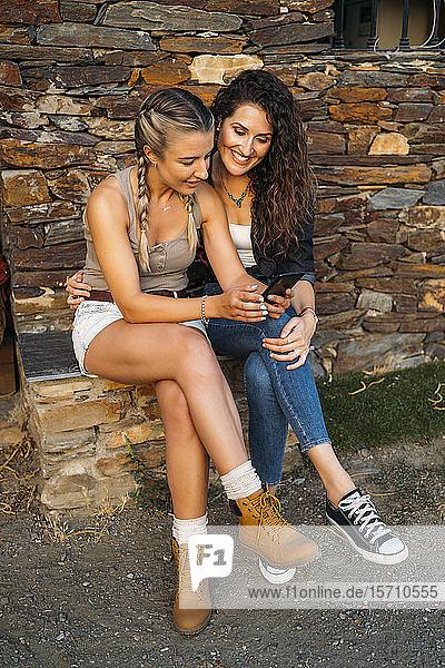Zwei glückliche Frauen mit einem Smartphone sitzen in einem Steinhaus