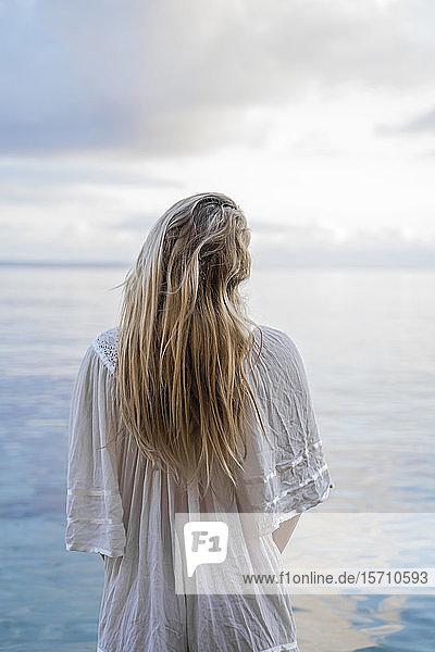 Rückenansicht einer jungen blonden Frau  die vor dem Meer steht  Ibiza  Balearen  Spanien