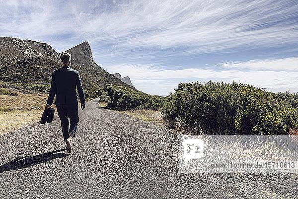 Rückansicht eines Geschäftsmannes  der barfuss auf einer Landstrasse geht  Cape Point  Western Cape  Südafrika