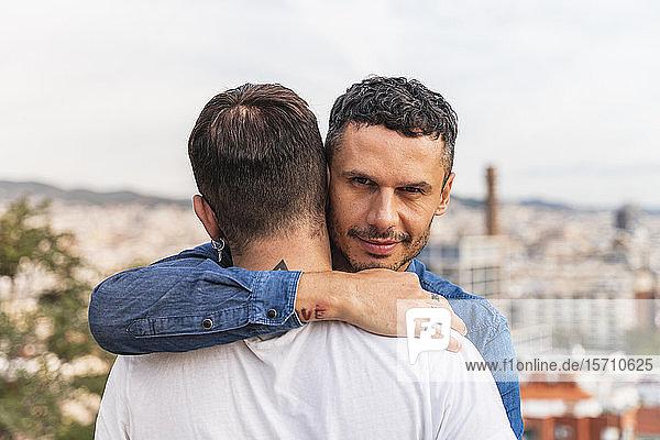 Porträt eines Mannes  der seinen Freund umarmt  Barcelona  Spanien