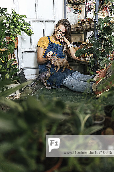 Young woman with dinosaur figurine sitting on the floor in a small shop with plants