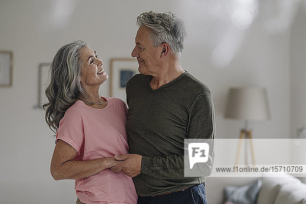 Happy senior couple in living room at home
