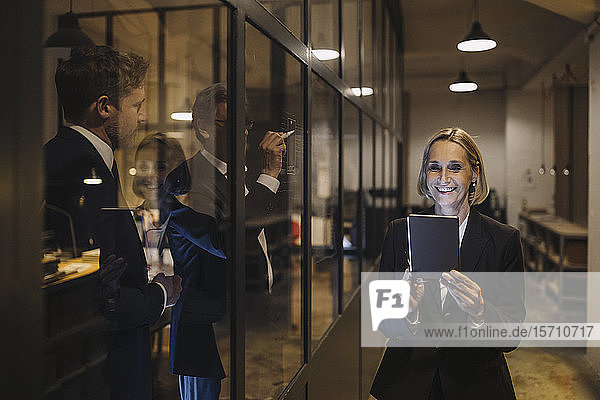 Smiling businesswoman using tablet and two businessmen working on drawing on glass pane in office