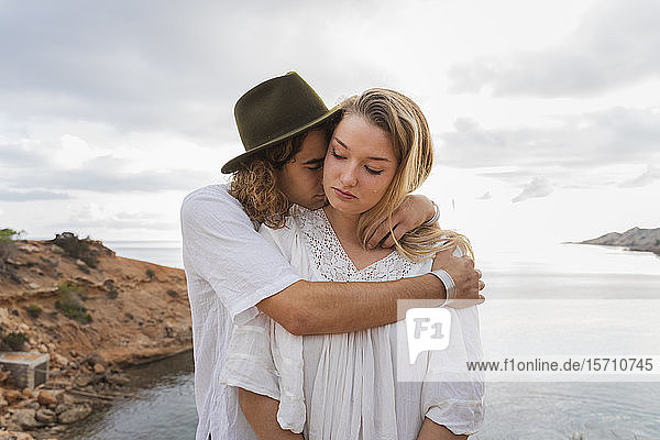 Junges verliebtes Paar steht vor dem Meer  Ibiza  Balearen  Spanien