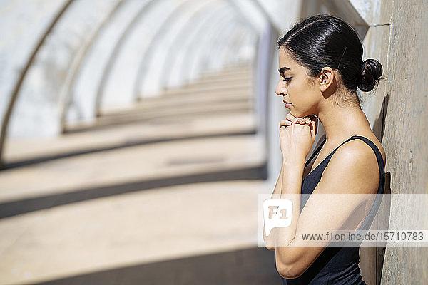 Junge Frau in schwarzem Badeanzug lehnt an einer Wand in einem Torbogen