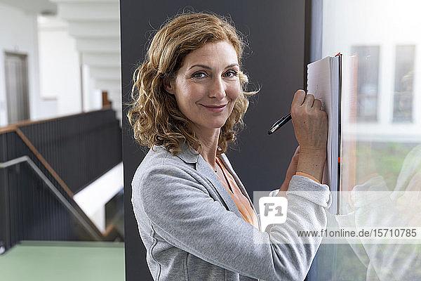 Porträt einer lächelnden Geschäftsfrau  die an einer Fensterscheibe im Büro Notizen macht