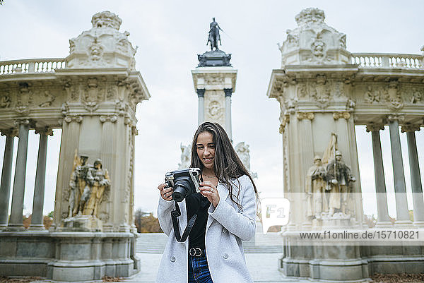 Smiling woman with a camera standing in front of Alfonso XII monument in El Retiro park  Madrid  Spain