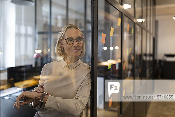 Mature businesswoman looking at adhesive notes on glass pane in office