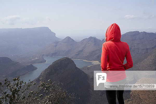 Woman standing on top of a hill enjoying the beautiful landscape below her  Blyde River Canyon  South Africa.