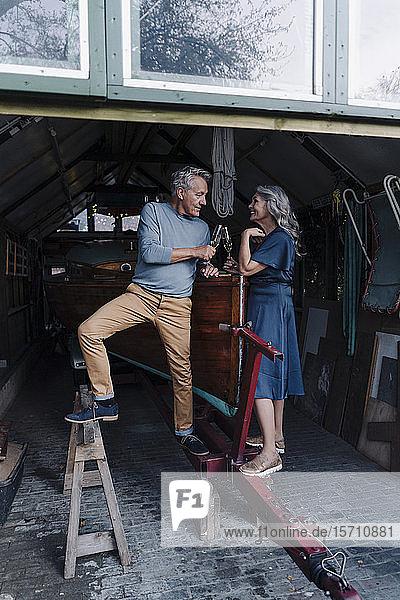 Älteres Ehepaar in einem Bootshaus  Champagnergläser klirrend