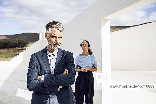 Geschäftsmann stehend mit verschränkten Armen  Frau lehnt an weißer Wand