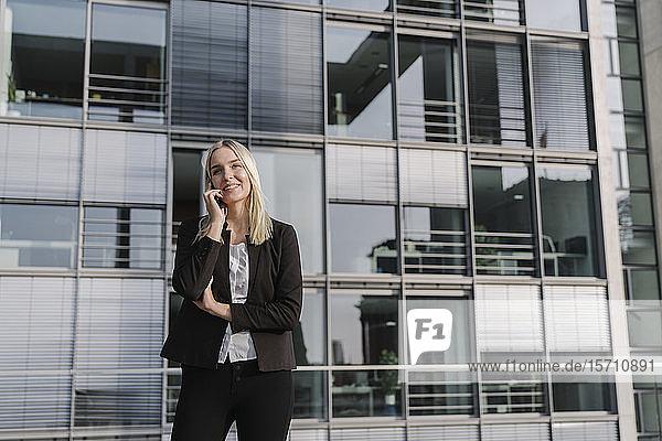Blonde Geschäftsfrau mit Smartphone im Hintergrund modernes Gebäude