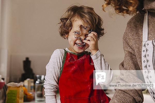 Verspieltes Mädchen mit ihrer Mutter,  die in der Küche einen Weihnachtsplätzchenausstecher hält