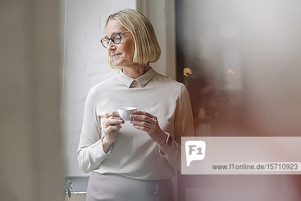 Mature businesswoman having a coffee break at the window in office